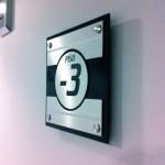 Placa PVC com Dibond, fixa por conectores metálicos.