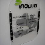 Placa acrílica com PVC e vinil, fixa por conectores metálicos.