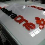 Logotipo em PVC com recorte CNC sobre placa acrílica.