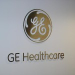 Logotipo GE Healthcare em inox escovado recortado em CNC, fixo à parede com espaçadores.